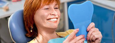 Woman looking at her smile in mirror at dentist's office