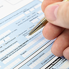 Close up of person filling out form with pen